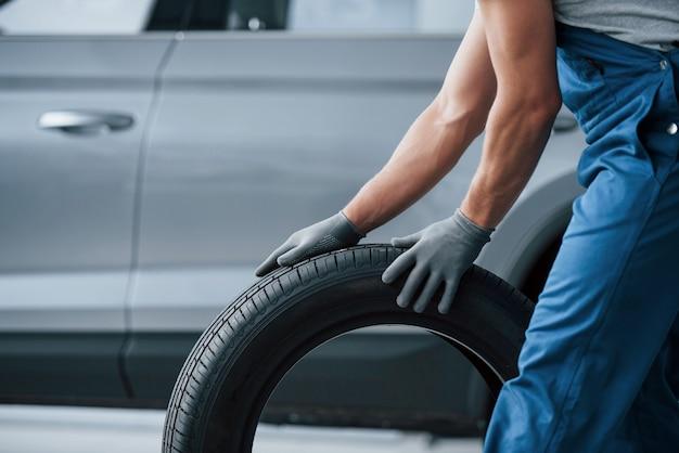 Arte del trasporto. meccanico che tiene un pneumatico al garage di riparazione. sostituzione di pneumatici invernali ed estivi Foto Gratuite