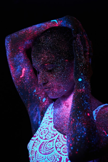 Art woman cosmos in ultraviolet light. entire body is covered with colored droplets. girl posing in the dark. noise, out of focus Premium Photo