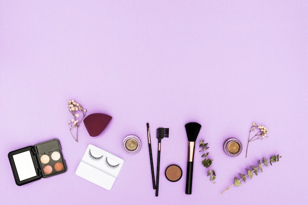 Artificial eyelashes; eyeshadow palette; blender; compact powder and makeup brushes with twig and gypsophila on purple background Free Photo