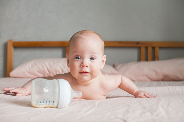 Artificial feeding. the baby lies on the bed on her tummy and looks at the feeding bottle in front of him with the adapted milk formula Premium Photo
