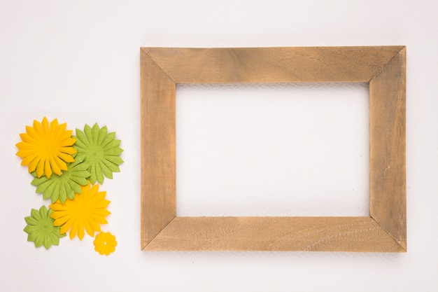 Artificial green and yellow flowers near the wooden empty frame on white backdrop Free Photo