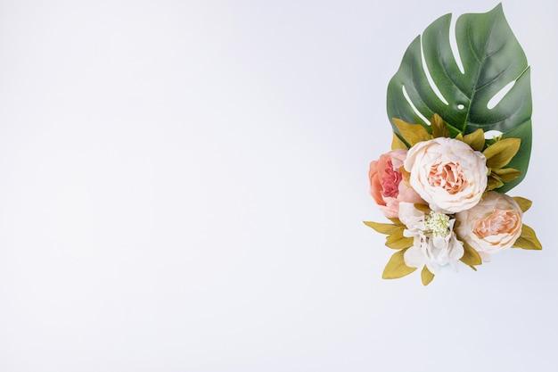 白い表面に人工葉と花の花束。 無料写真