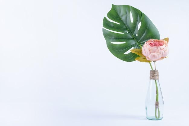 인공 잎과 흰색 유리 항아리에 꽃. 무료 사진