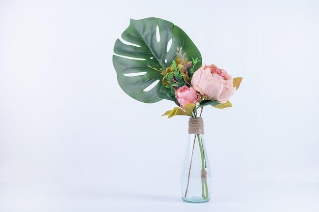 白のガラス瓶の人工葉と花。 無料写真