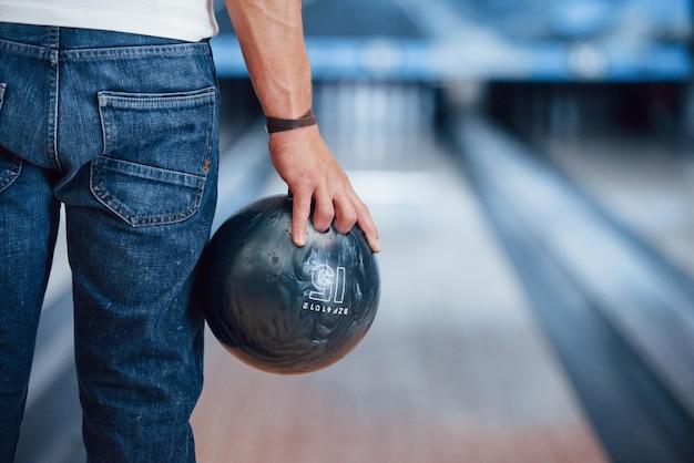 Illuminazione artificiale. vista posteriore delle particelle dell'uomo in abiti casual che giocano a bowling nel club Foto Gratuite