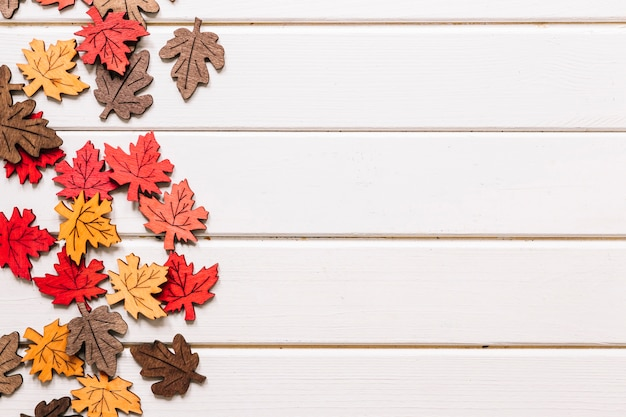 Artificial maple leaves on white wooden background Free Photo