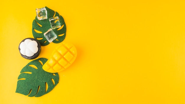An artificial monstera leaves; mangosteen; ice cubes and mongo slice against yellow background Premium Photo
