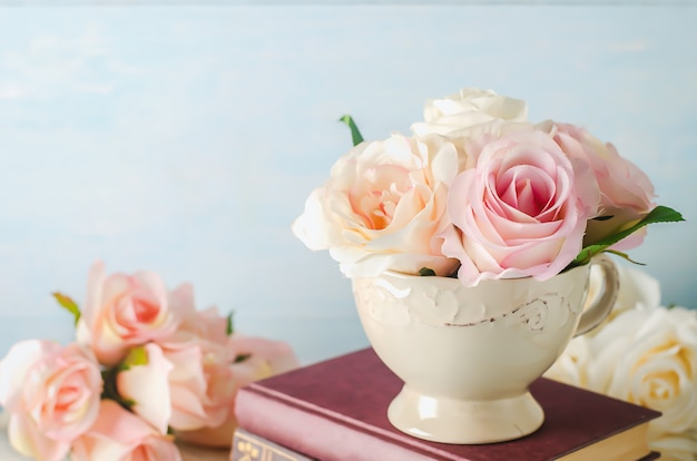 Artificial pink rose flowers in vintage cup with books on blue Premium Photo