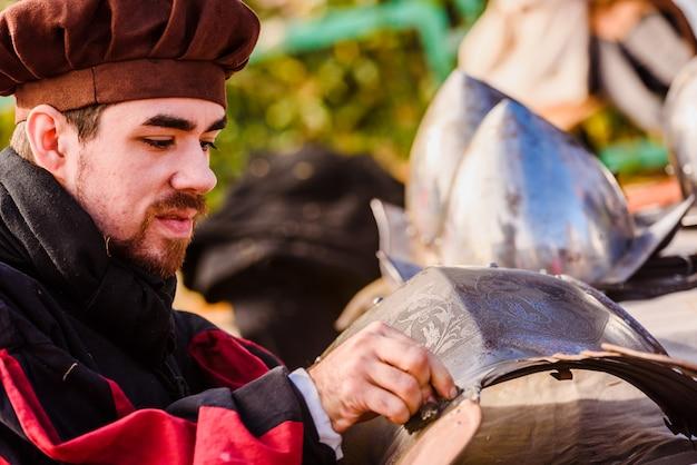 Artisans disguised as medieval era burnishing dirty armor to clean them. Premium Photo