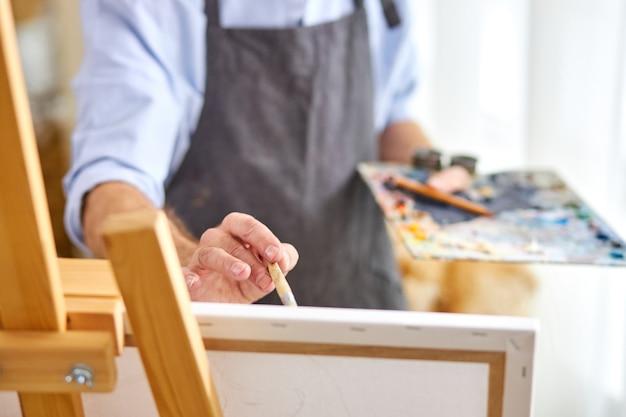 그림 붓으로 캔버스에 그림을 그리는 작가, 상상력이 넘치는 마음, 작업 중 창의적인 화가. 근접 촬영, 손에 초점 프리미엄 사진