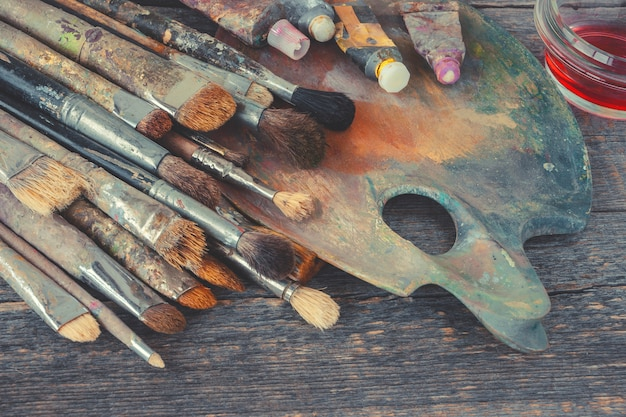 Artist brushes and tubes with paint on the palette Premium Photo