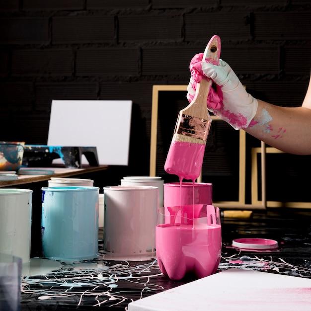Художник окуная кисть в розовой краске Premium Фотографии