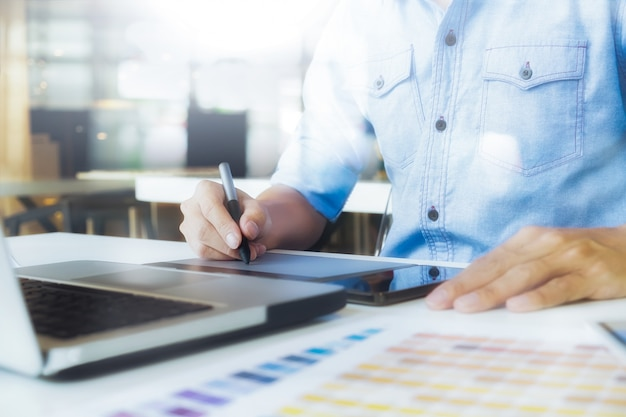 Artist drawing on graphic tablet with color swatches in office. architectural drawing with work tools and accessories. Free Photo