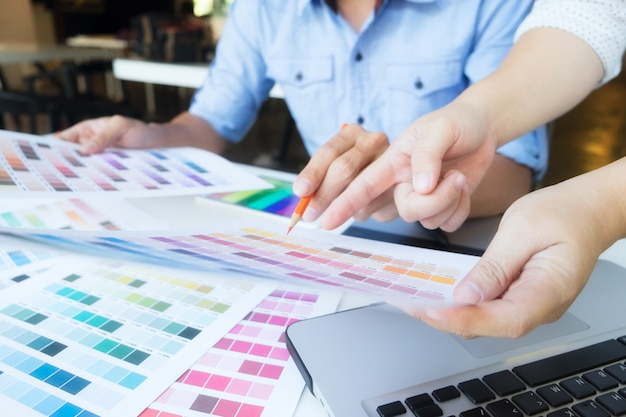 Artist drawing on graphic tablet with color swatches in office. Free Photo