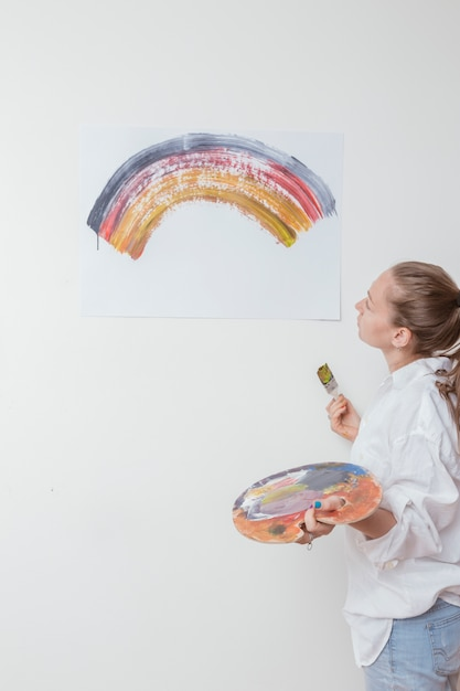 Artist looking at picture of rainbow in studio Free Photo