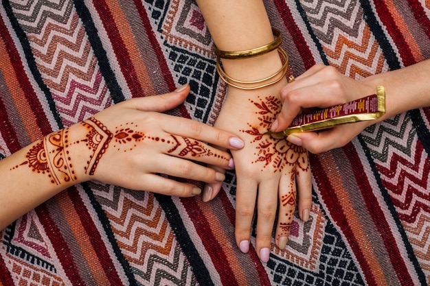 Artist making mehndi on womans hand on bright table Free Photo