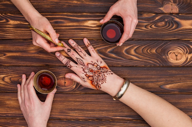 Artist making mehndi on womans hand and drinking tea Free Photo