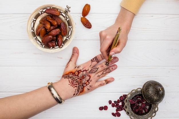Artist making mehndi on womans hand near dates fruit Free Photo