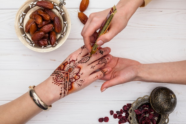 Artist making mehndi on womans hand near dried dates fruit Free Photo