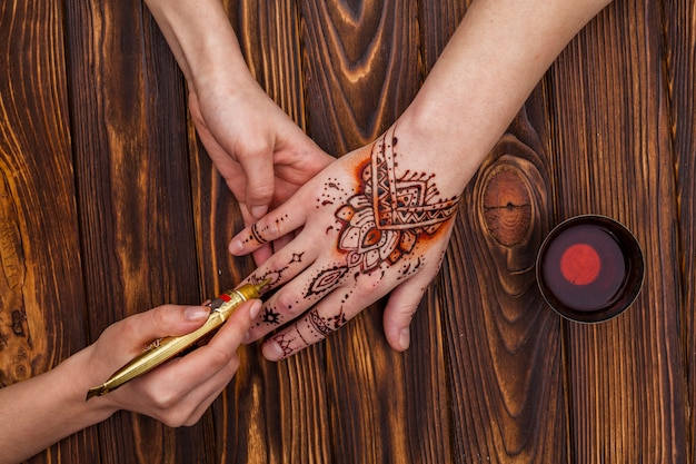 Artist making mehndi on womans hand near tea cup Free Photo