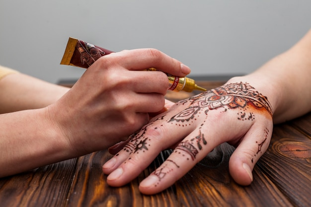 Artist making mehndi on womans hand on table Free Photo