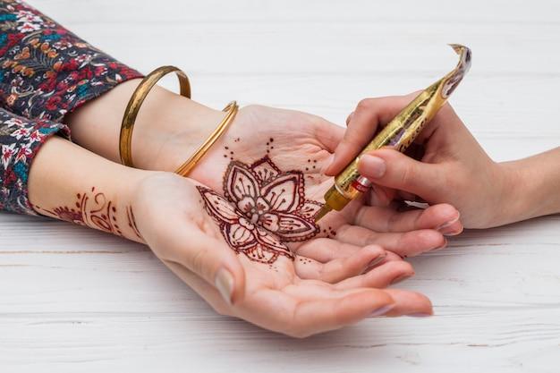Artist making mehndi on womans palms Free Photo