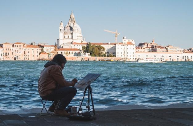 昼間にイタリアのヴェネツィアの運河を描くアーティスト 無料写真