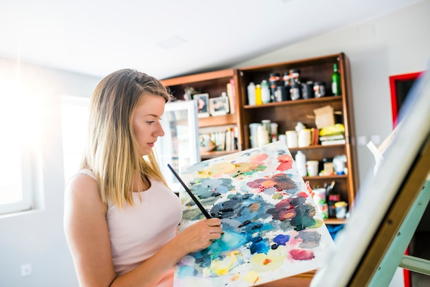 Artist paints a picture of oil paint brush in hand with palette. Premium Photo