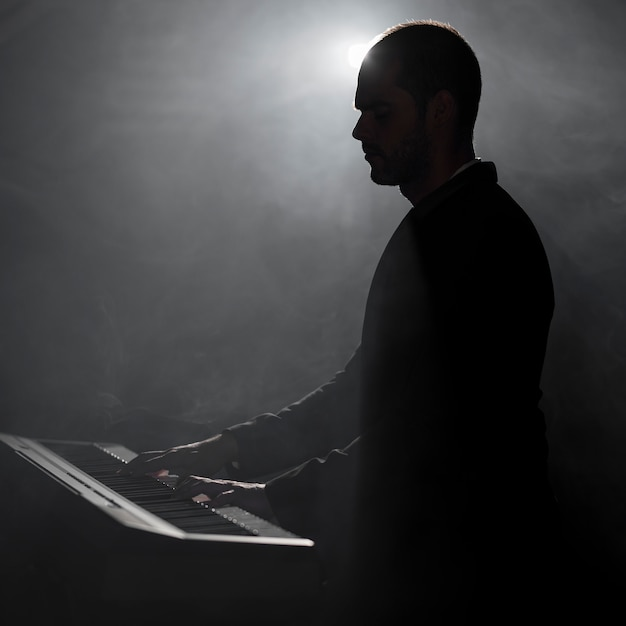 Artist playing piano smoke and shadows effects Free Photo