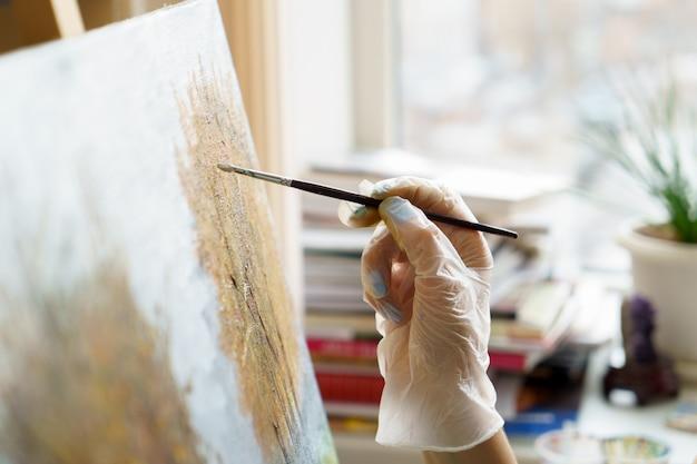 Artist's hand draws oil painting close up Premium Photo