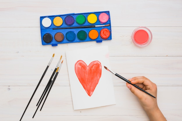 Artist's hand holding paint brush on hand drawn heart shape painting over wooden surface Free Photo