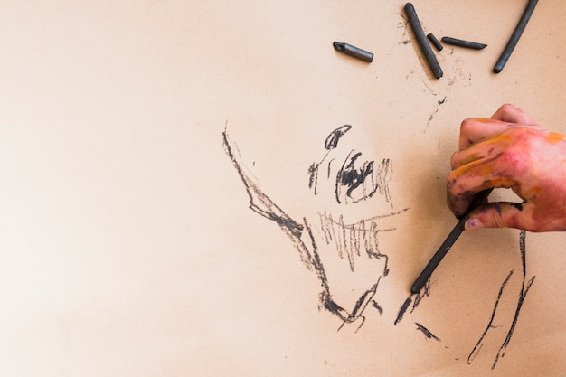 Artist's hand sketching drawing with charcoal on paper Free Photo