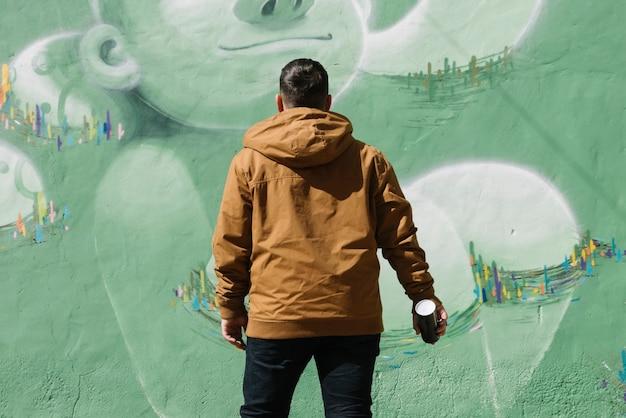 Художник, стоящий перед стенами граффити с аэрозолем, может в руке Бесплатные Фотографии