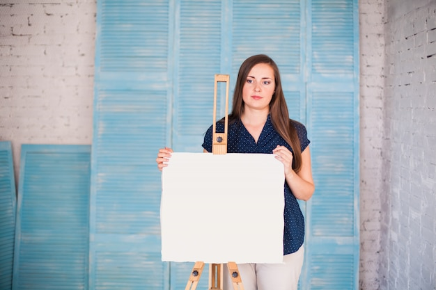 Artist with white canva in her studio Premium Photo