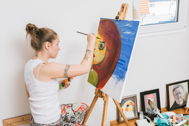Artist working with picture in workshop Free Photo