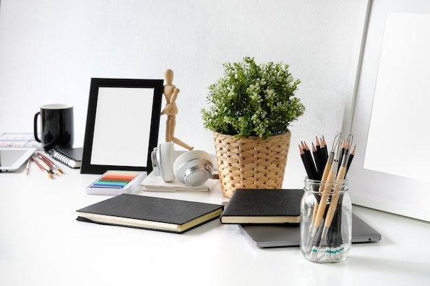 Artist workplace table with pencil, sketch book, photo frame and plant decoration. Premium Photo