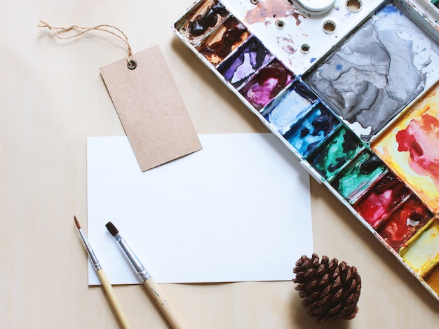 Artist workspace mock up with brush and paint on blank card Free Photo
