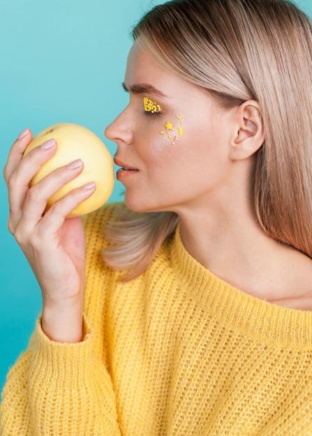 Artistic model holding fruit Free Photo