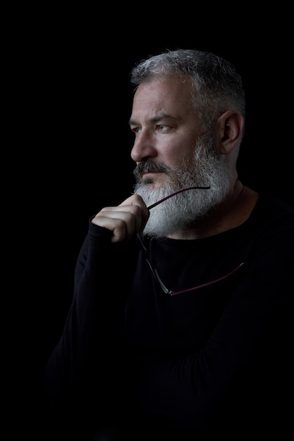 Artistic portrait of a brutal gray haired man with a beard and glasses on a black background, selective focus Premium Photo
