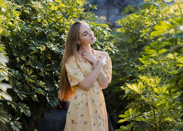 Artistic shot of a posing woman in a greenhouse Free Photo