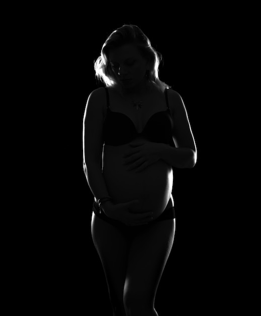 Artistic silhouette of blonde pregnant woman on isolated background Premium Photo