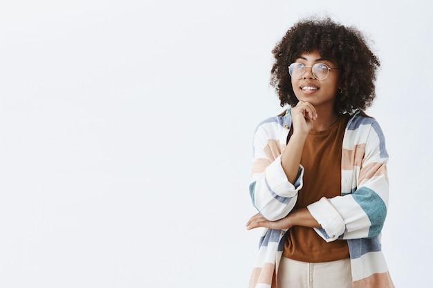 Художественно стильная и креативная привлекательная темнокожая женщина в прозрачных очках и модном наряде, стоящая в задумчивой позе, глядя в верхний левый угол с рукой на подбородке Бесплатные Фотографии