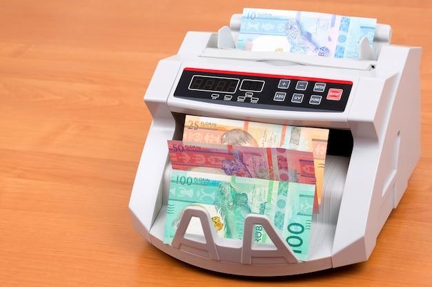 Aruban florin in a counting machine Premium Photo