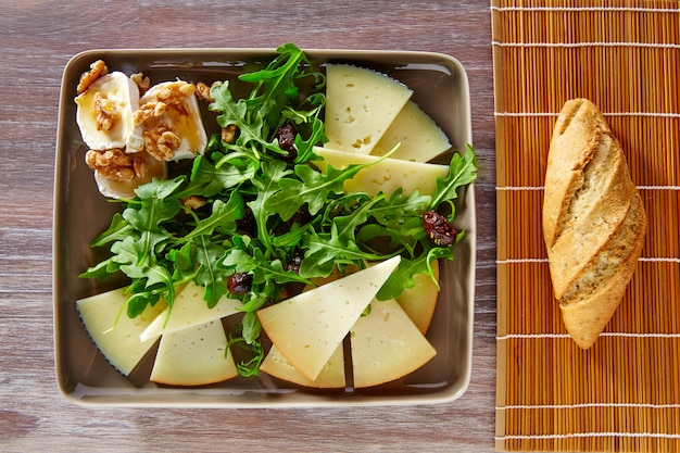 Arugula salad with goat cheese honey and nuts Premium Photo