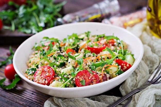 木製の背景の上にキノア、arugula、大根、トマト、キュウリとサラダ。 Premium写真