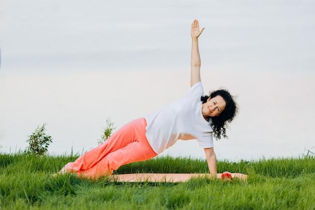 Старшая женщина делая планку стороны asana йоги внешнюю. , йога Premium Фотографии