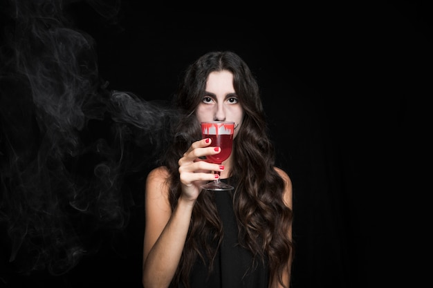 Ashy woman closing face by goblet with smoking red liquid Free Photo