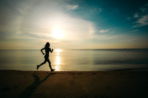 Asia beautiful woman in sport ware ready to  exercising by running on the beach. silhouette style. Premium Photo