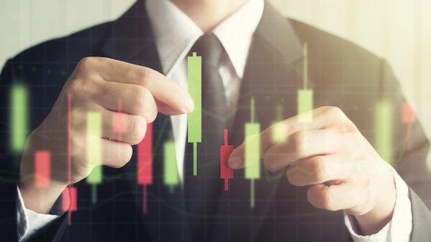 Asia business male holding candlestick graph make from paper red and green Premium Photo