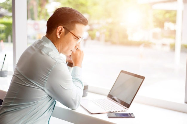 Asia business man working with laptop while sitting coffee shop Premium Photo
